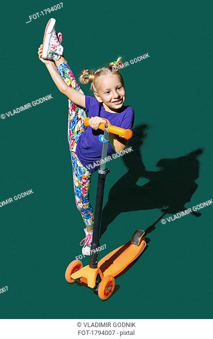 Playful girl with scooter doing standing splits on green background