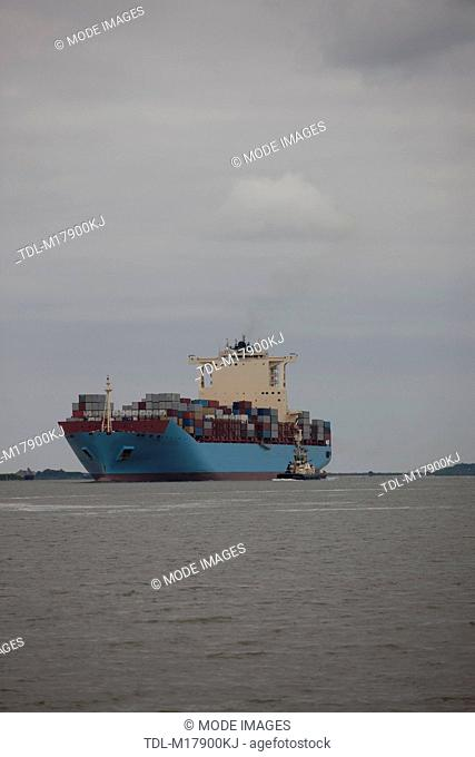 A container ship being escorted to port by a tug boat