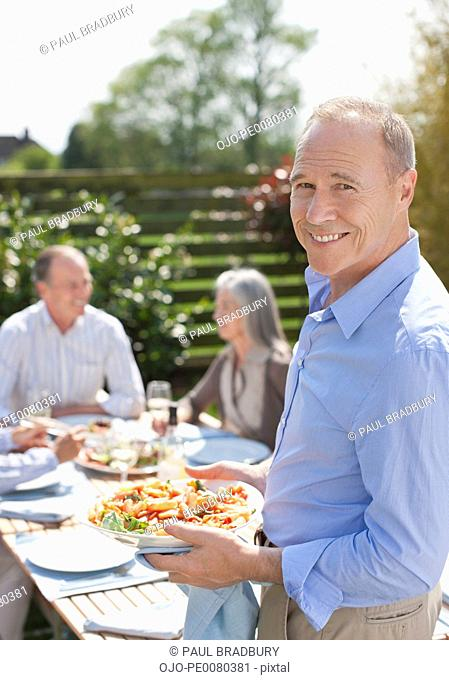 Portrait of smiling man enjoying lunch with friends on patio