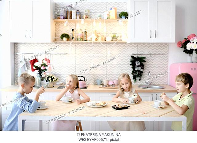 Four children eating cookies at kitchen table