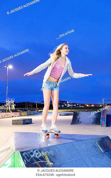 Young woman with skateboard at night