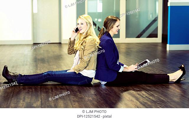 Two beautiful young women who are millennial business professionals sitting back to back on the floor of their workplace using technology; Sherwood Park
