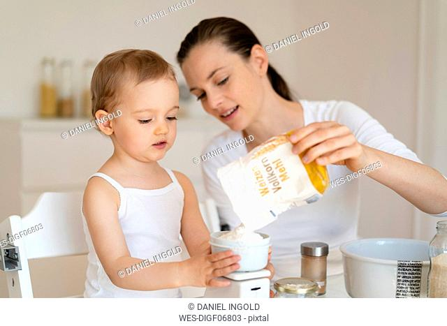 Mother and little daughter making a cake together in kitchen at home weighing flour