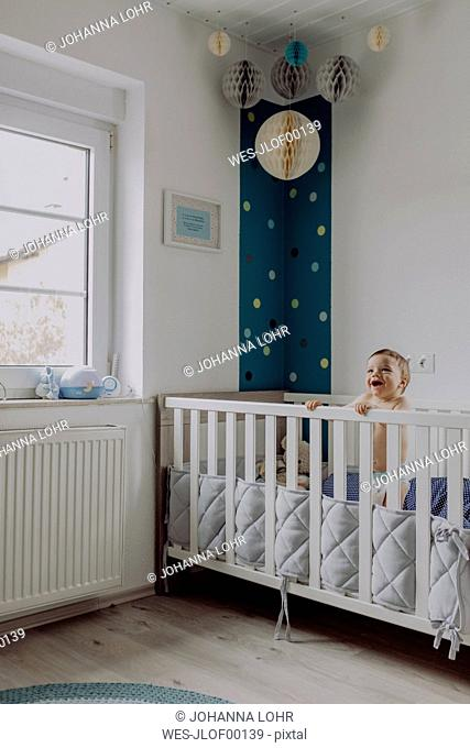 Baby boy standing in his cot, laughing