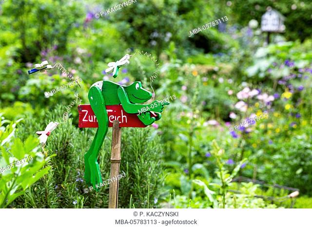 Sign with green frog showing the way to the garden and pond, Germany