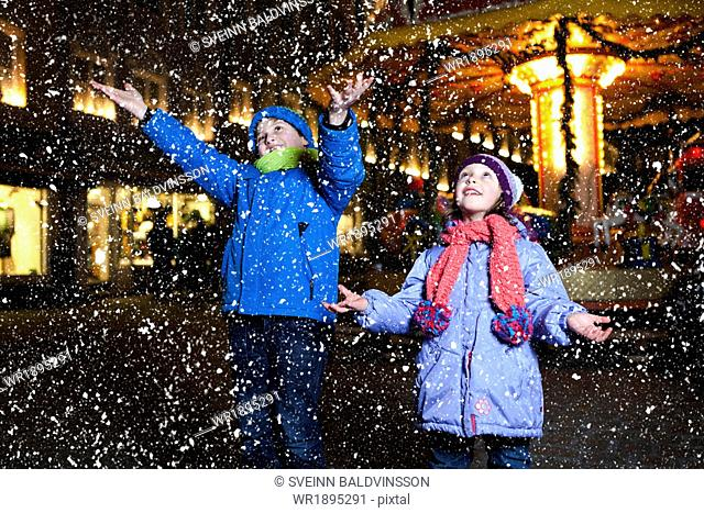 Children catching snow at Christmas Market in Bad Toelz, Bavaria, Germany
