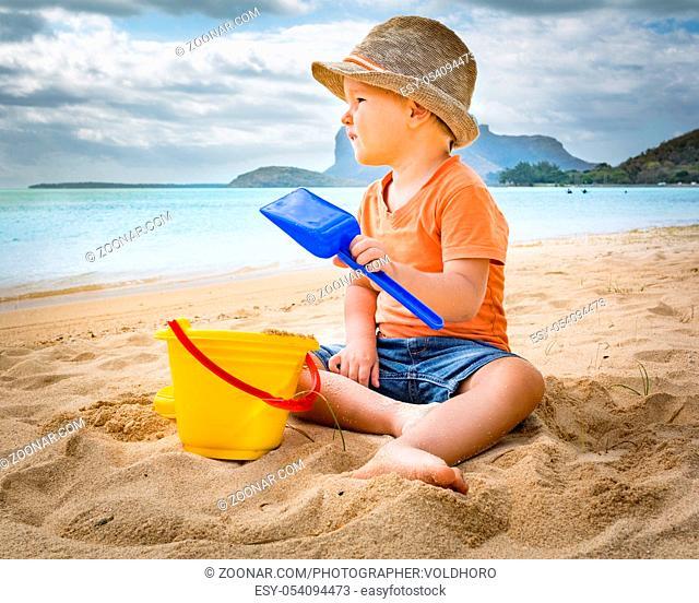 Cute boy on the tropical beach playing toys
