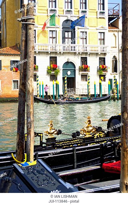 Gondolas on sunny canal in front of architectural building in Venice, Italy