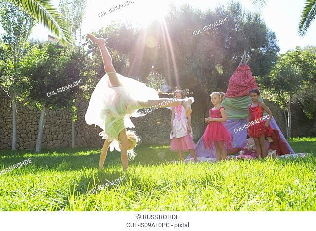 Girls watching friend in fairy costume doing cartwheel in garden
