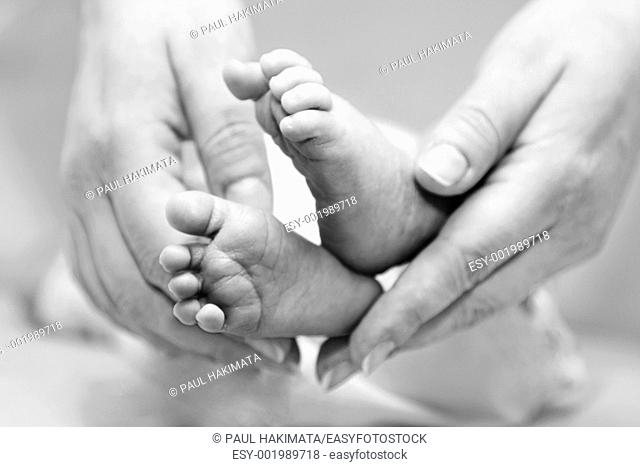 Mother's gentle touch holding cute baby feet