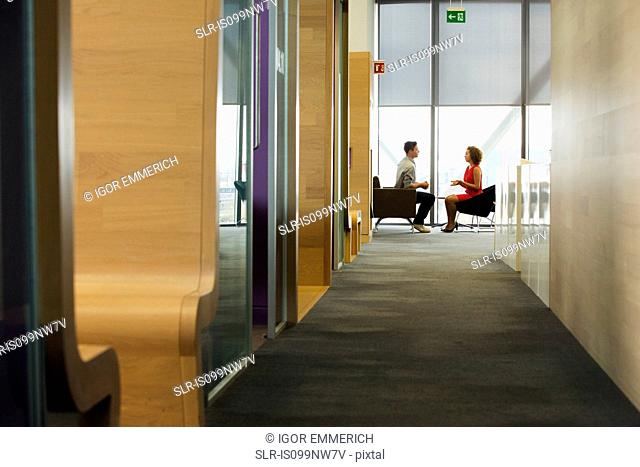Young woman and man in meeting in office