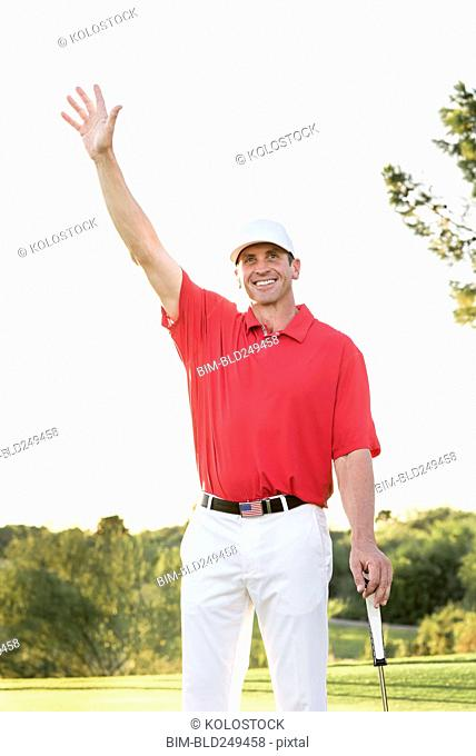 Hispanic golfer waving on golf course