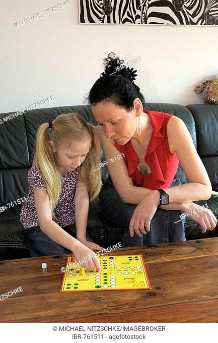 Mother with child, 10 years old, playing Ludo board game