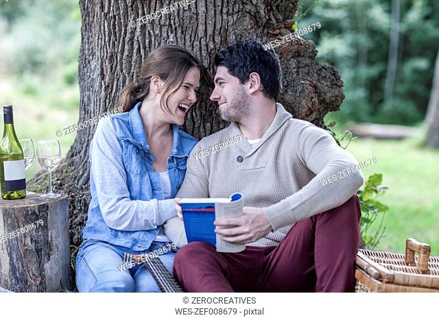 Happy young couple having a picnic with white wine