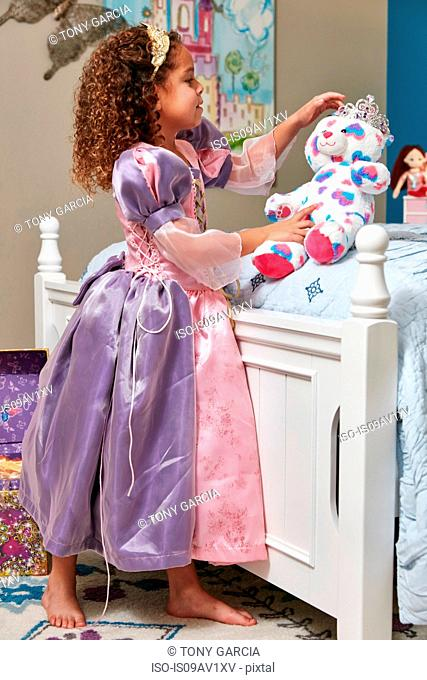 Side view of girl dressed up as princess play acting with teddy bear