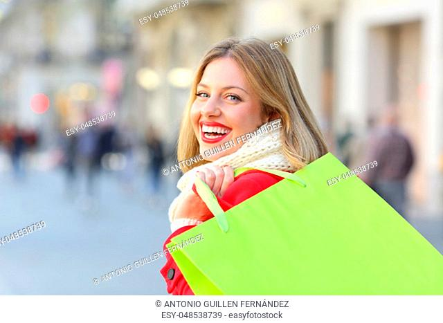Back view portrait of a shopper holding blank shopping bags walking on the street