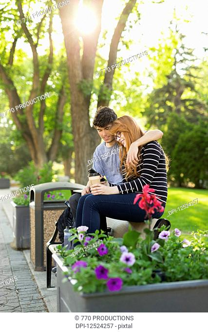 A young couple sitting together on a bench in a park and checking social media on a smart phone; Edmonton, Alberta, Canada