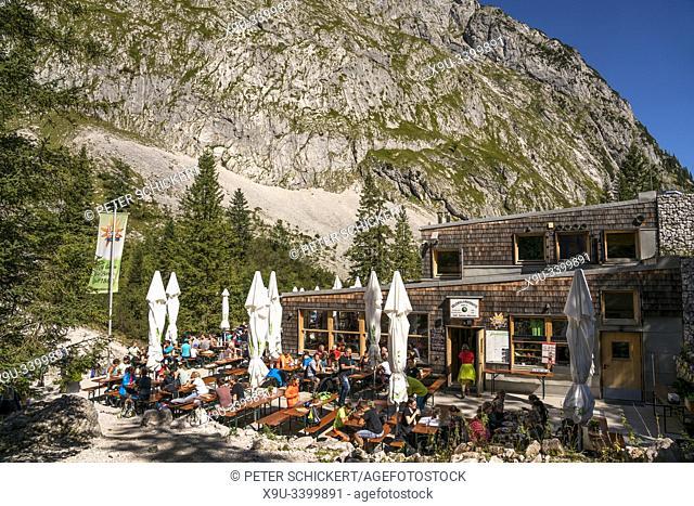 Wanderer auf der Terrasse der Berghütte Höllentalangerhütte im Höllental bei Grainau, Garmisch-Partenkirchen, Oberbayern, Bayern