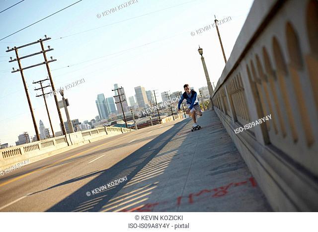 Man skateboarding on pedestrian walkway
