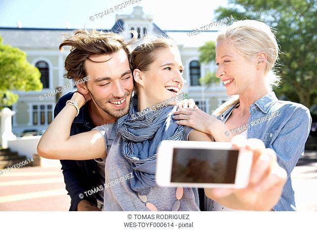 Happy friends outdoors taking a selfie