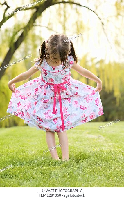 Young girl modeling a floral dress; Toronto, Ontario, Canada
