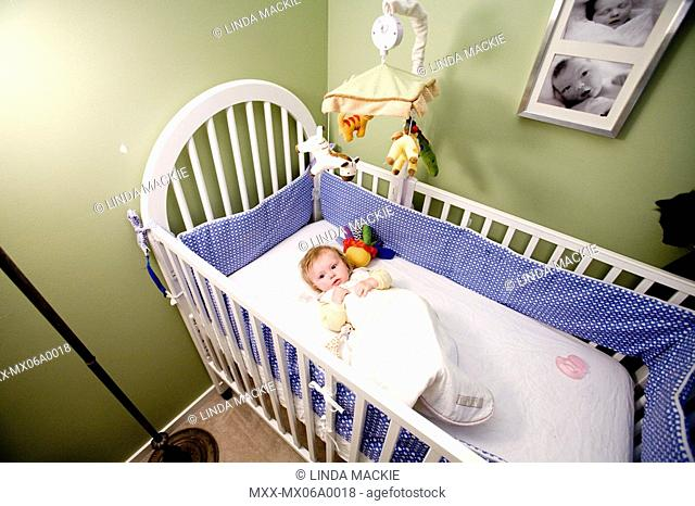 Wide shot of baby in crib