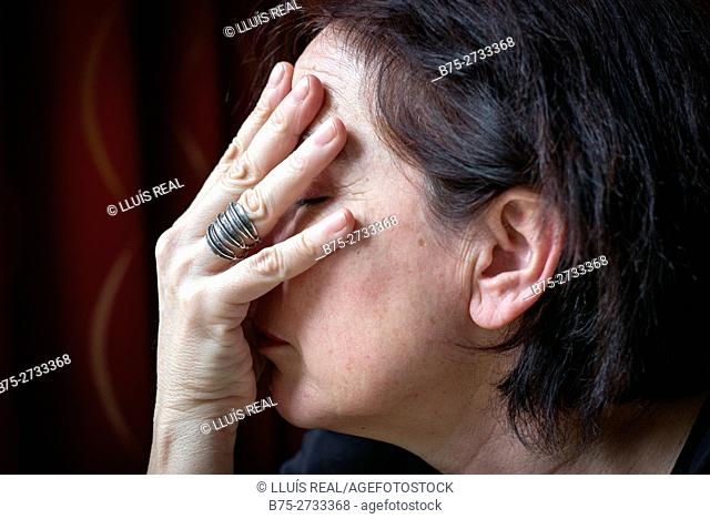 Middle-aged woman's profile covering her face with her hand