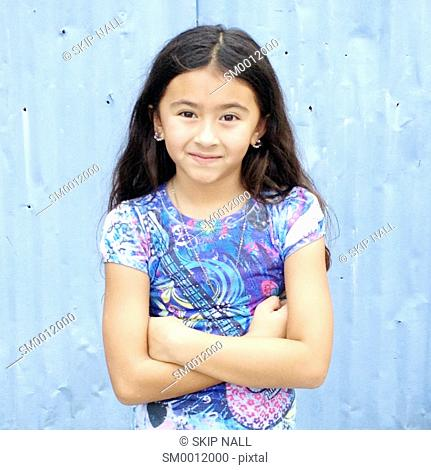 Little girl smiling with her arms crossed looking at the camera