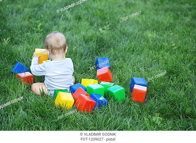 Baby in the garden with building blocks