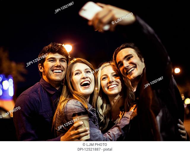 Two young couples stand closely together on the street at nighttime to pose for a self-portrait with a smart phone; Edmonton, Alberta, Canada