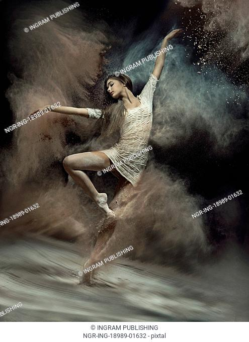Pretty ballet dancer with dust in the background