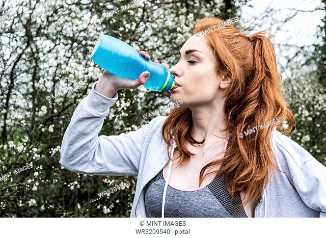Young woman with long red hair wearing sports kit, exercising outdoors, drinking from water bottle