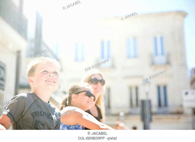 Family sitting in Piazza S. Oronzo, Lecce, Italy