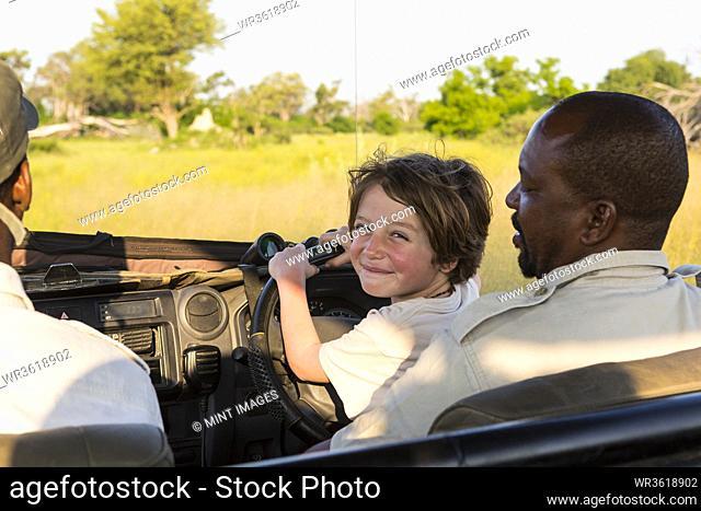smiling 6 year old boy steering safari vehicle, Botswana