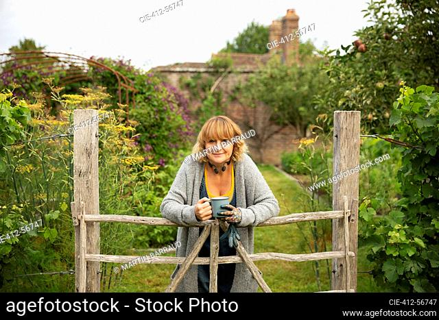 Portrait confident woman with tea at gate in idyllic cottage garden
