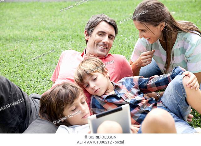 Family with two children spending afternoon at park, young boys using digital tablet