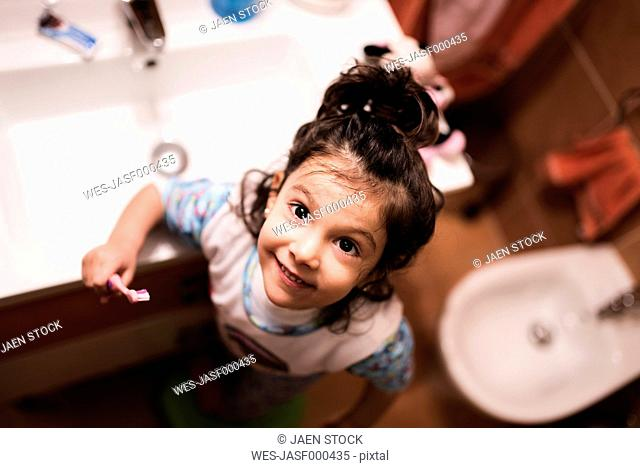 Portrait of smiling little girl standing in the bathroom going to brush her teeth
