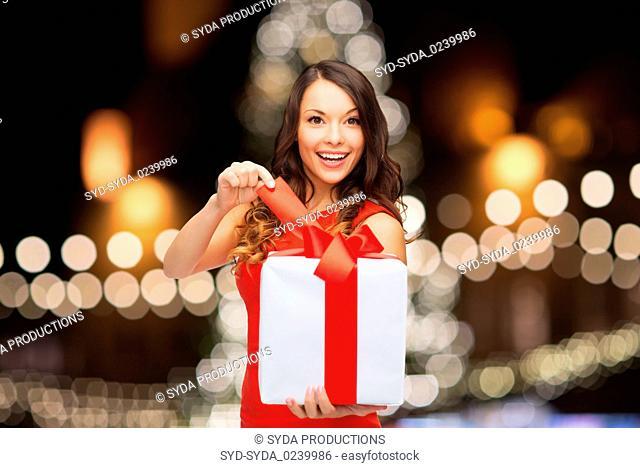 woman with gift box over christmas tree lights