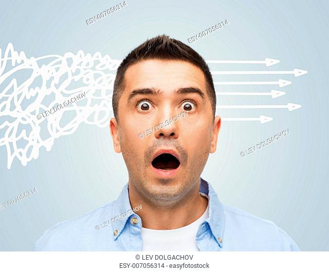 fear, emotions, horror and people concept - scared man with big eyes and open mouth shouting over gray background