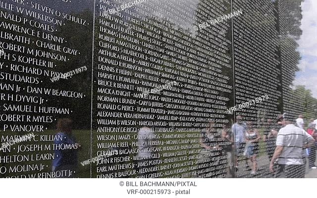 Tourists looking at friends name at reflections of hero names of war dead at Vietnam Veterans Memorial Wall monument in Washington DC