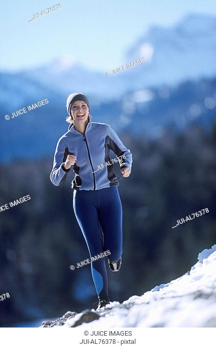 Portrait of a young woman jogging in winter setting