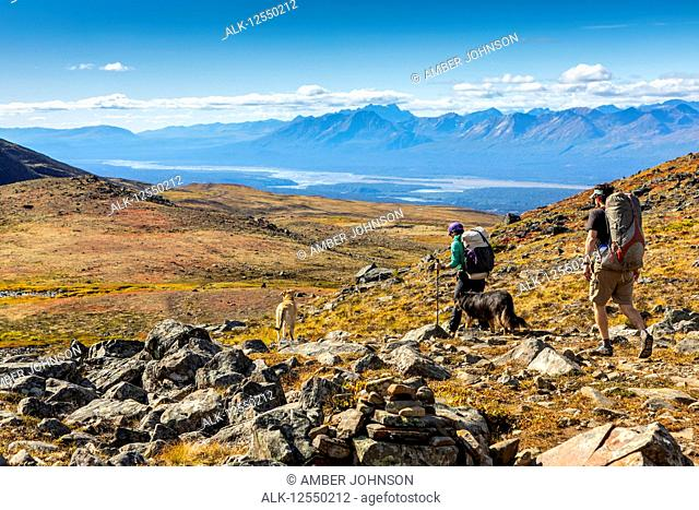 Man and woman backpacking on the tundra with dogs on the Kesugi Ridge Trail, Denali State Park, South-central Alaska; Alaska, United States of America