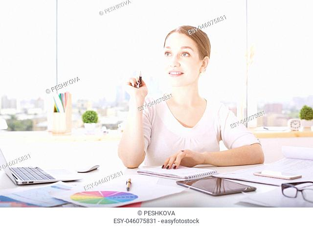 Portrait of attractive thoughtful young lady sitting at office desk with electronic devices and paperwork