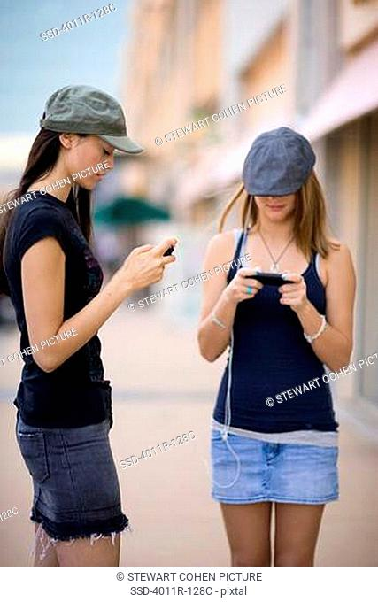 Two female friends listening to MP3 players