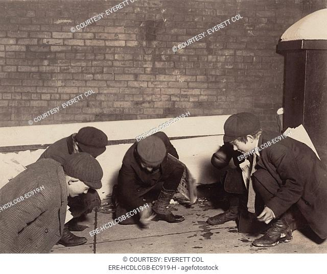 Children playing a dice game, from original caption: 'playing craps in the jail alley at 10 P.M.', Albany, New York, photograph by Lewis Wickes Hine, February