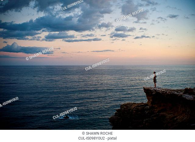 Woman standing on cliff looking out to sea at sunset