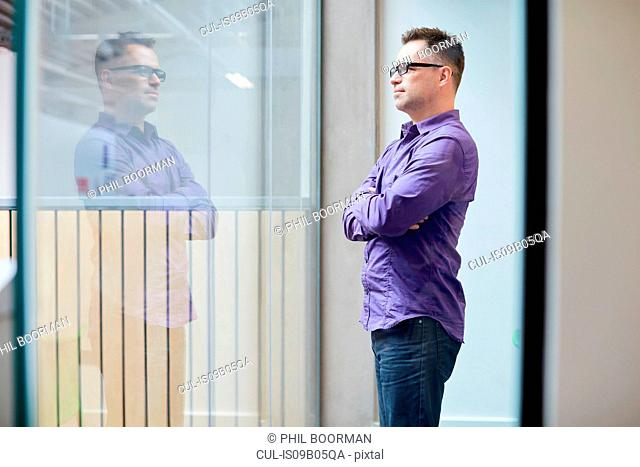 Male designer looking out from window in design studio