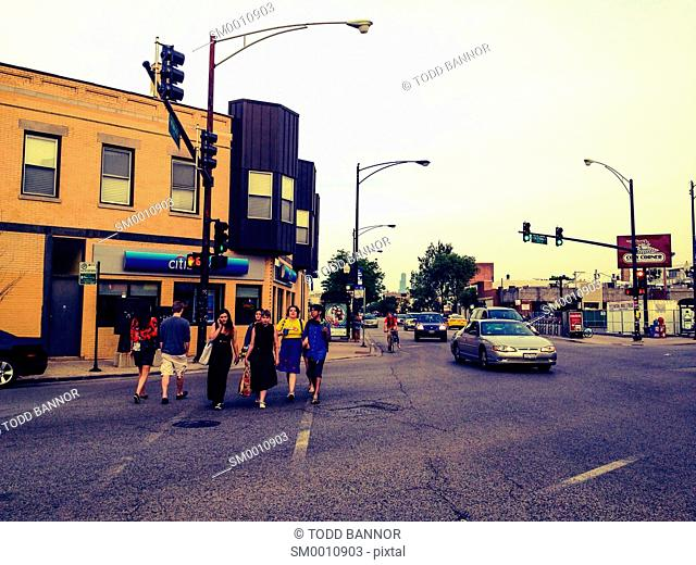 View southeast on Milwaukee Avenue at California Avenue, Logan Square neighborhood of Chicago. Pedestrians in crosswalk, one using mobile phone