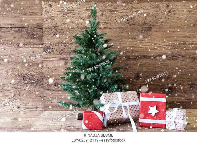 Christmas Card For Seasons Greetings. Christmas Tree With Gifts Or Presents In The Front Of Wooden Background With Snowflakes. White Ribbon With Bow