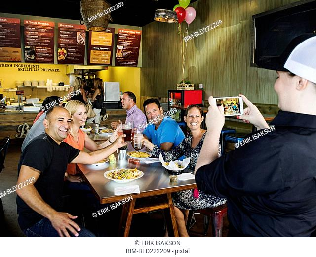 Man photographing friends in cafe